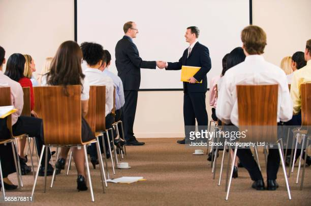 Businessmen shaking hands for audience in presentation