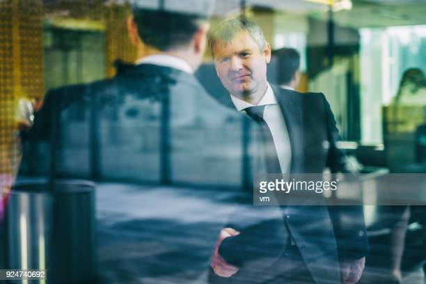 Businessmen shaking hands in an office lobby