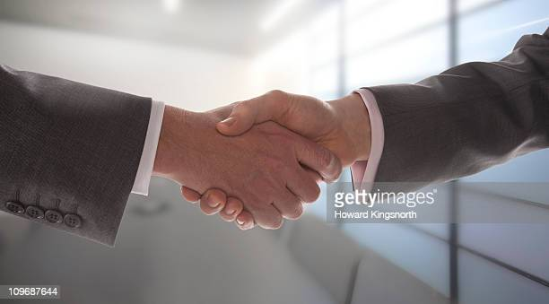 2 businessmen shaking hands in boardroom - stock trader stock pictures, royalty-free photos & images