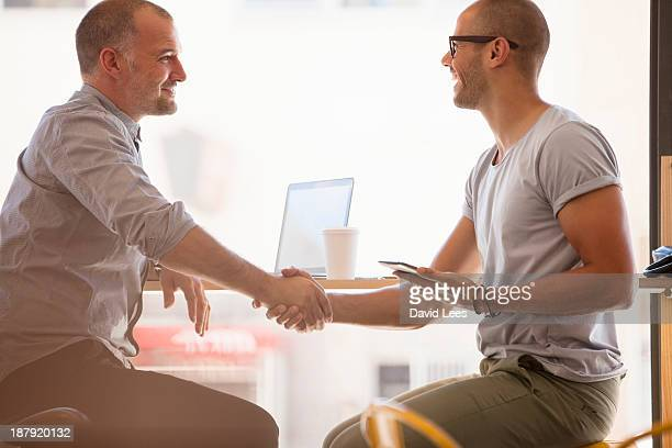 Businessmen shaking hands in cafe