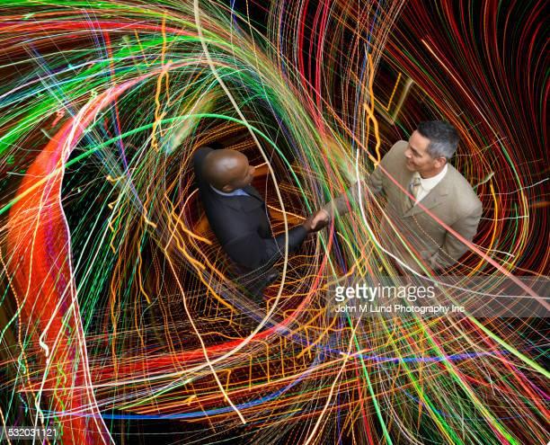 businessmen shaking hands in colorful light beams - miglioramento digitale foto e immagini stock