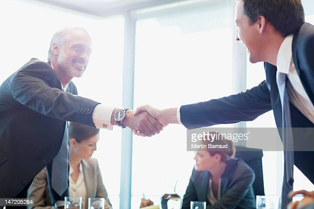 businessmen shaking hands in conference room - gelegenheid stockfoto's en -beelden