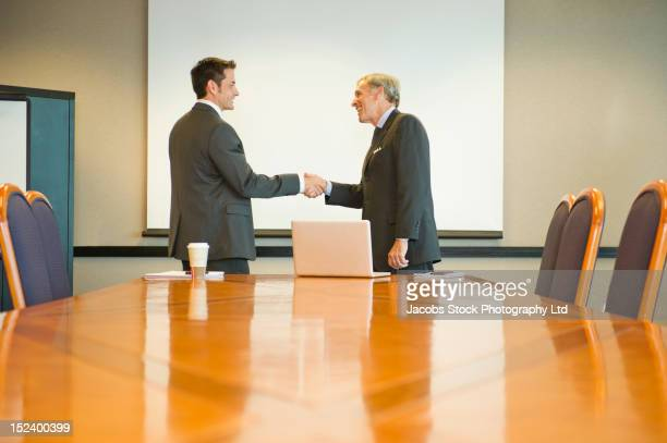 businessmen shaking hands in conference room - sells arizona stock pictures, royalty-free photos & images