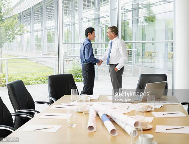 businessmen shaking hands in conference room - deal england stock photos and pictures