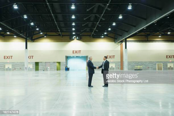 businessmen shaking hands in empty warehouse - sells arizona stock pictures, royalty-free photos & images