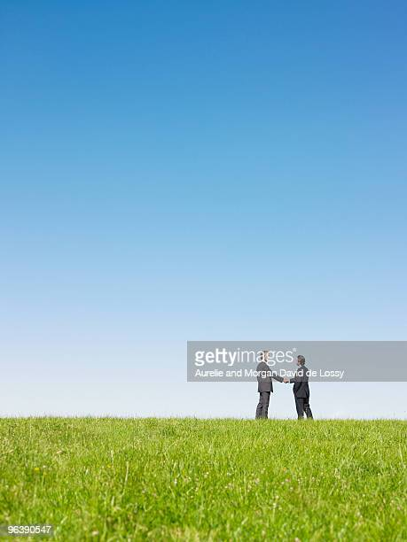 businessmen shaking hands in field