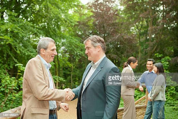 Businessmen shaking hands in forest