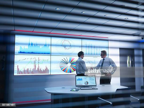 Businessmen shaking hands in front of graphs on screen in meeting room