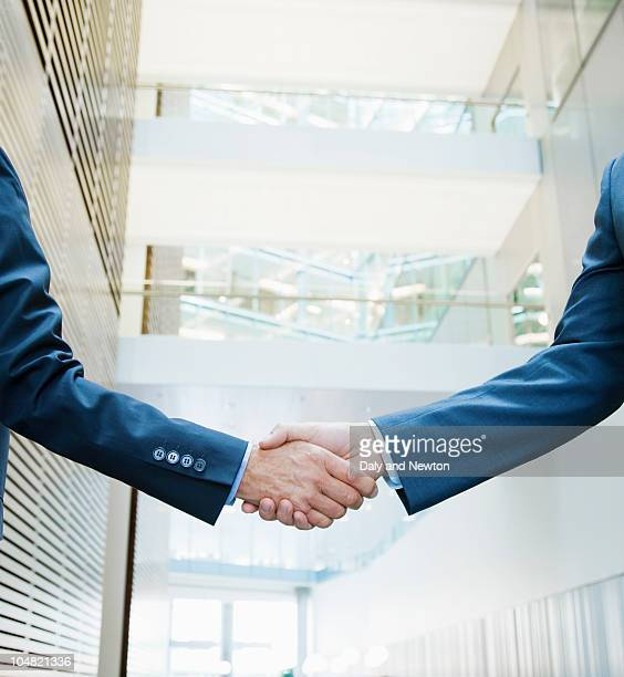 businessmen shaking hands in lobby - handshake stock pictures, royalty-free photos & images