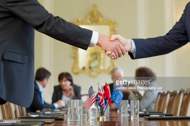 businessmen shaking hands in meeting - politics stock-fotos und bilder