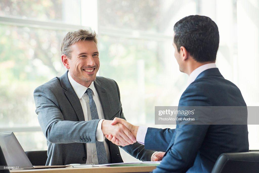 Businessmen shaking hands in meeting : Stock Photo