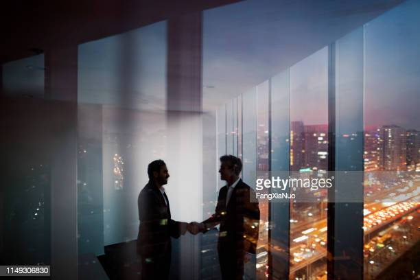 businessmen shaking hands in office at night - successor stock pictures, royalty-free photos & images