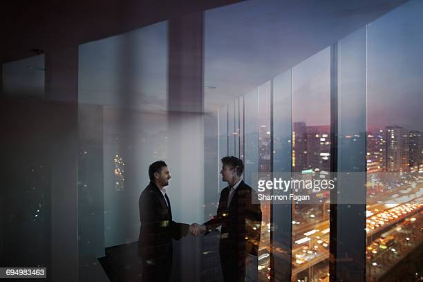 Businessmen shaking hands in office at night