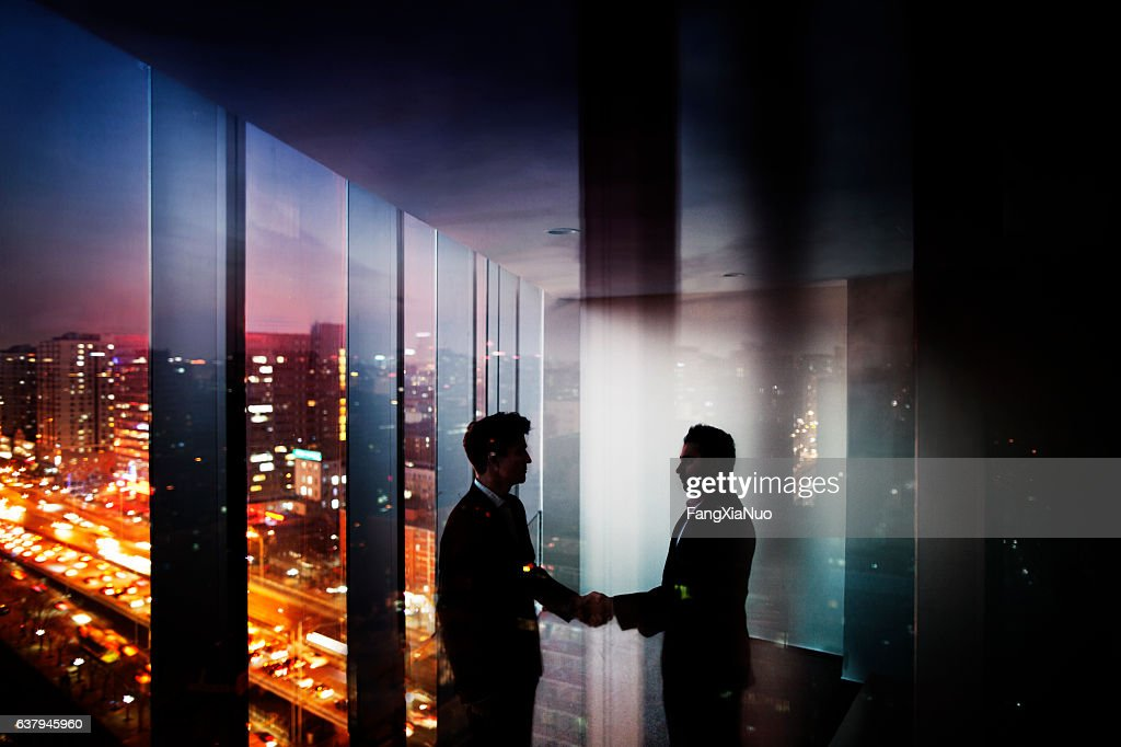 Businessmen shaking hands in office at night with city view : Stock Photo