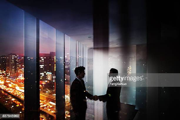 businessmen shaking hands in office at night with city view - mystery stock pictures, royalty-free photos & images