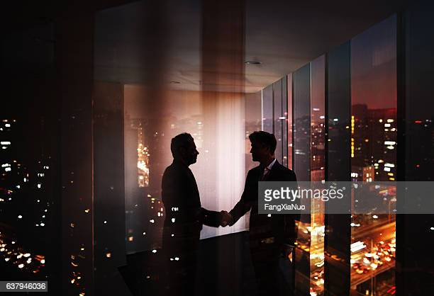 Businessmen shaking hands in office at night with city view