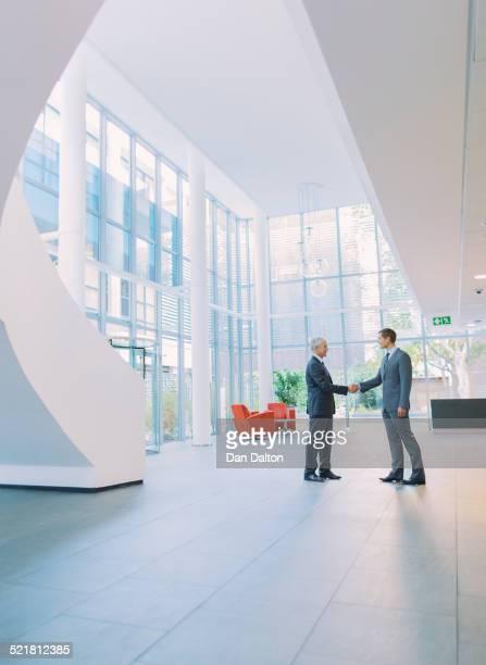 Businessmen shaking hands in office building