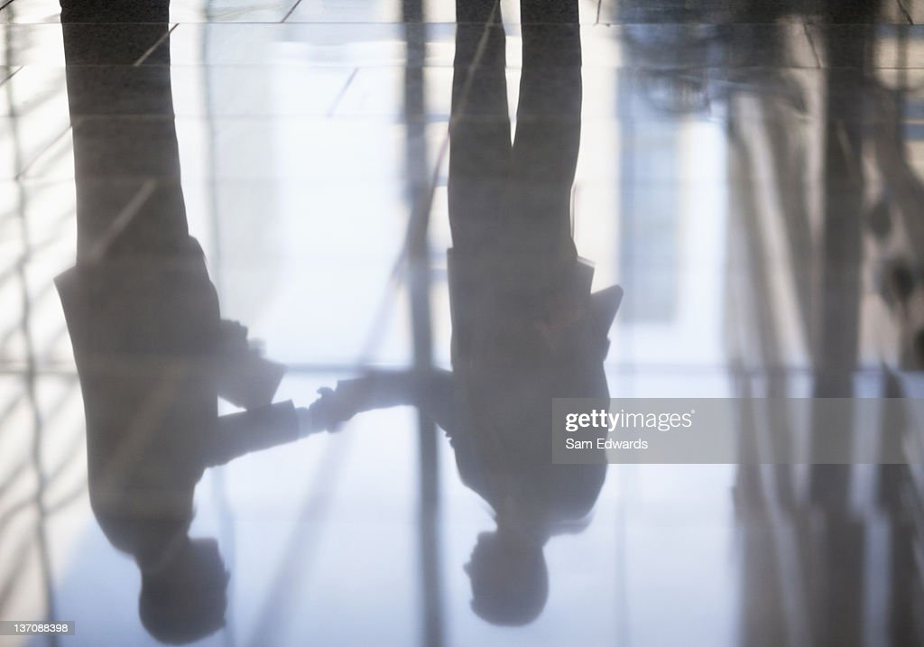 Businessmen shaking hands in office lobby : Stock Photo