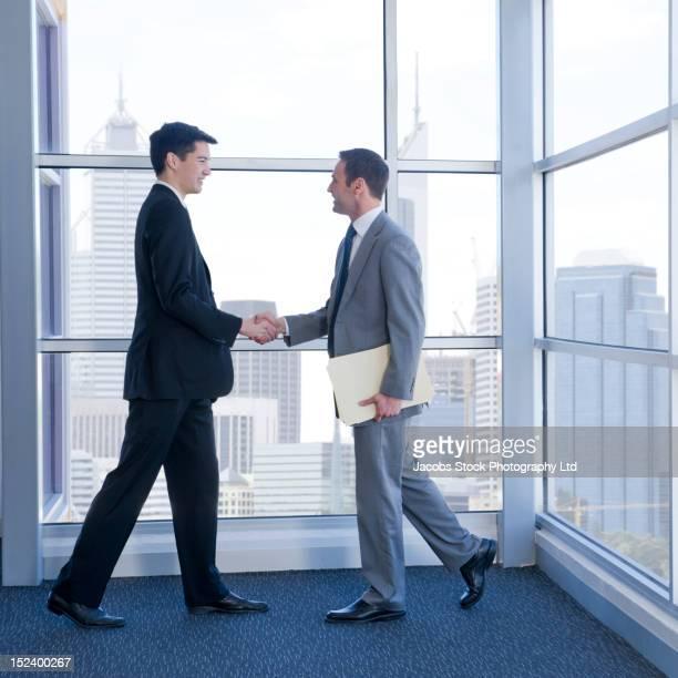 businessmen shaking hands in office - formelle geschäftskleidung stock-fotos und bilder