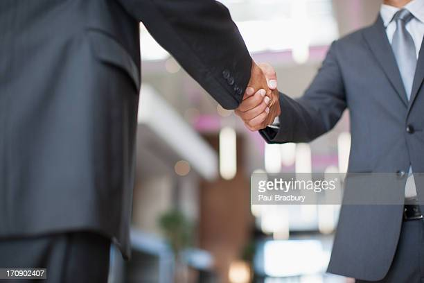 businessmen shaking hands in office - full suit stock pictures, royalty-free photos & images