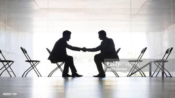 Geschäftsleuten beim Händeschütteln im Büro