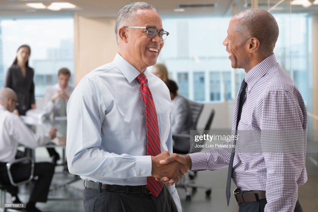 Businessmen shaking hands in office : Foto stock