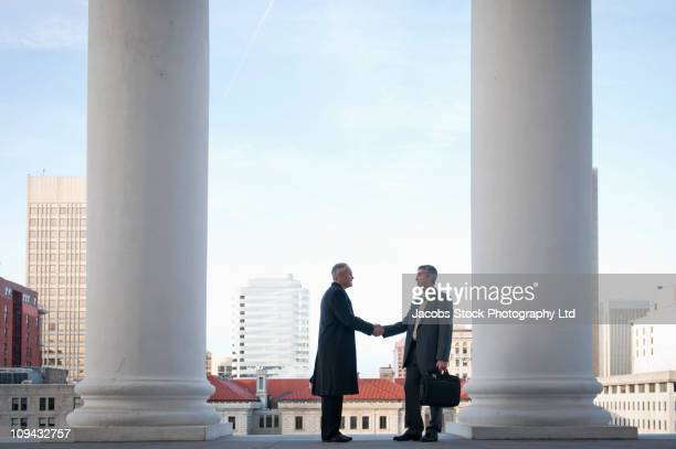 Businessmen shaking hands near pillars