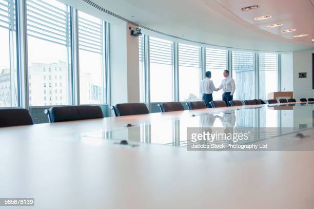 Businessmen shaking hands near window in office conference room