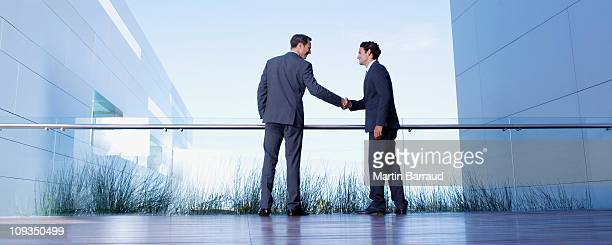 businessmen shaking hands on balcony - blue suit stock pictures, royalty-free photos & images