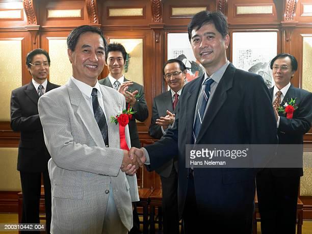 Businessmen shaking hands, others applauding, portrait