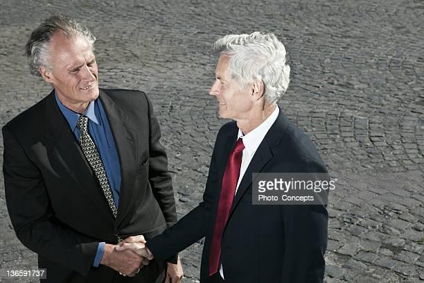 Businessmen shaking hands outdoors