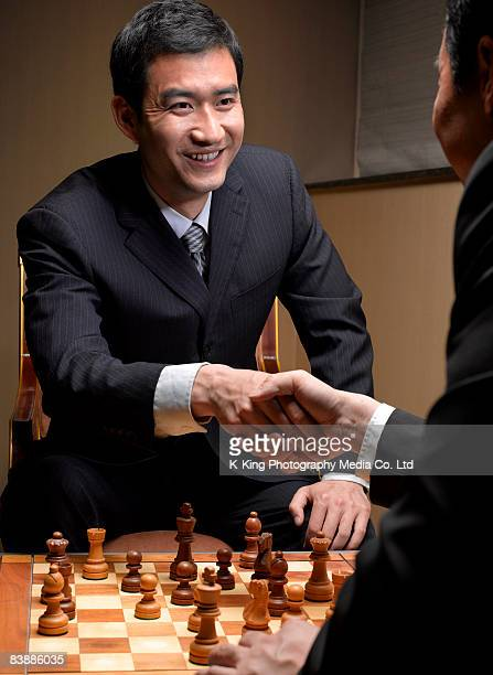 Businessmen shaking hands over chess board.