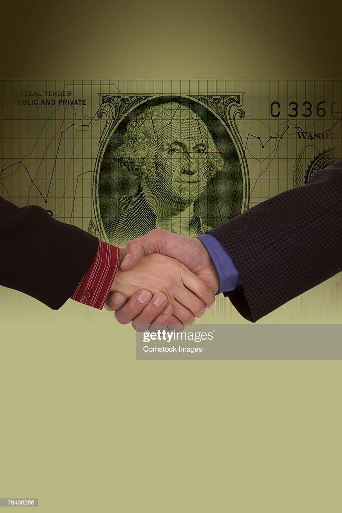 Businessmen shaking hands over money : Stockfoto