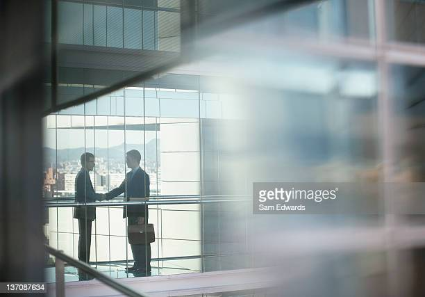 businessmen shaking hands - distant stock photos and pictures