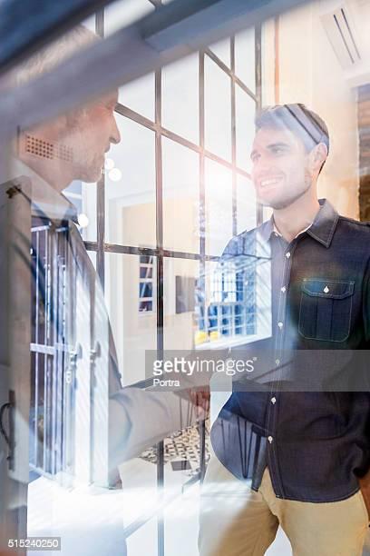 Geschäftsleute Händeschütteln durch Glas