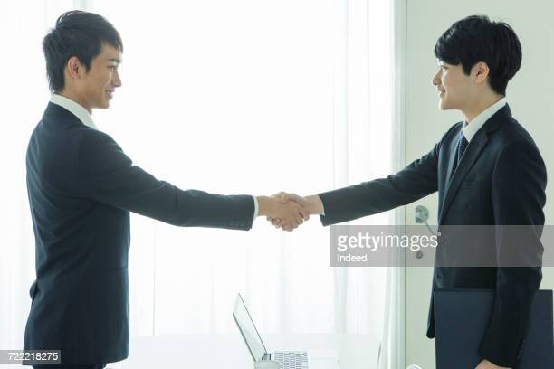 Businessmen shaking hands, smiling face to face