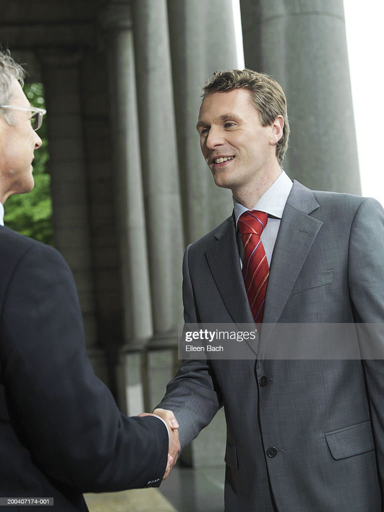 Businessmen shaking hands, smiling : Stock Photo