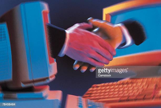 Businessmen shaking hands through computer monitors