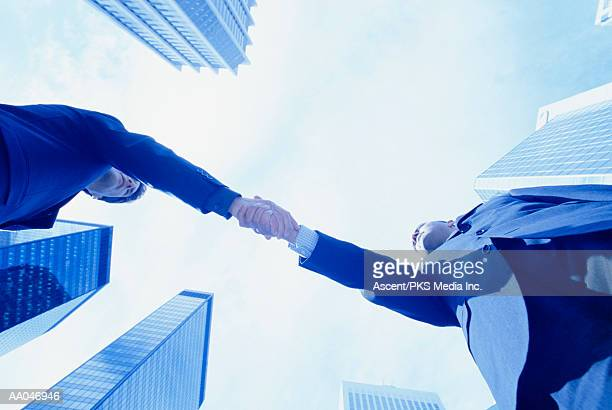 Businessmen shaking hands, view from below