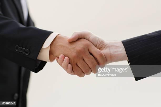 Businessmen shaking hands, view of hands