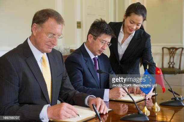 businessmen signing books in meeting - 外交 ストックフォトと画像