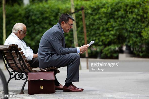 Businessmen sit on a bench and read papers near the Madrid stock exchange or Bolsas y Mercados on the day of a 10year bond sale in Madrid Spain on...