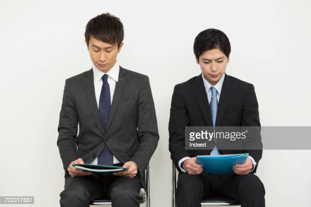 Businessmen sitting and reading document on chair