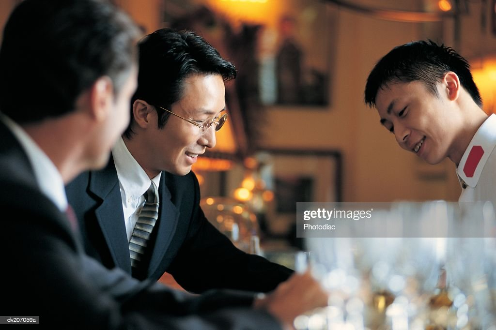 Businessmen sitting at bar : Stock Photo