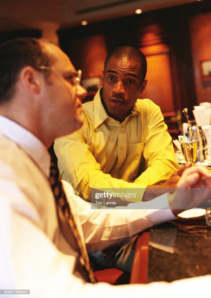 Businessmen sitting at bar talking, side view. : Stockfoto