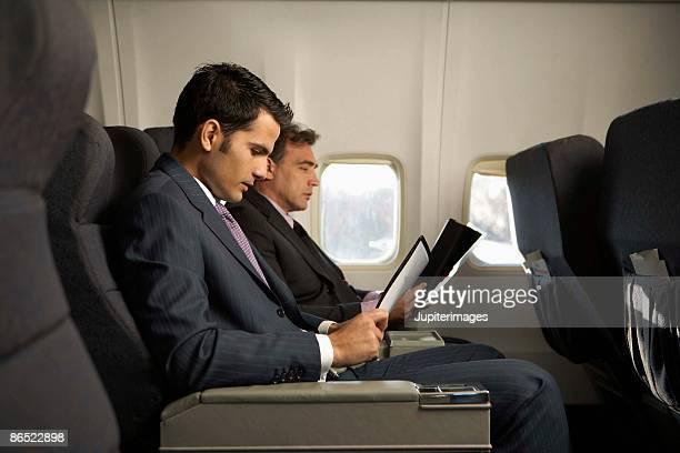 Businessmen sitting on airplane
