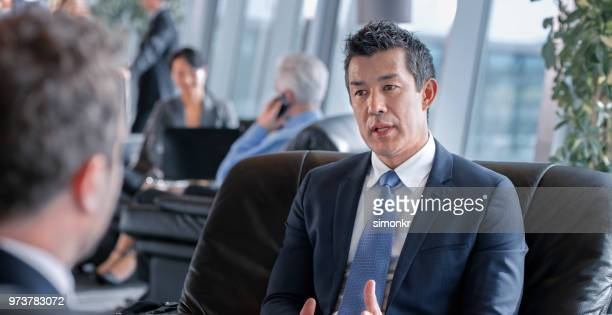 Businessmen sitting on chair at airport