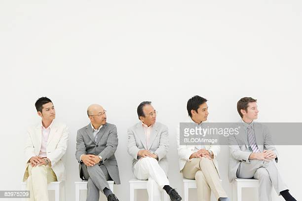 Businessmen sitting on chairs in row against wall, looking right, legs crossed