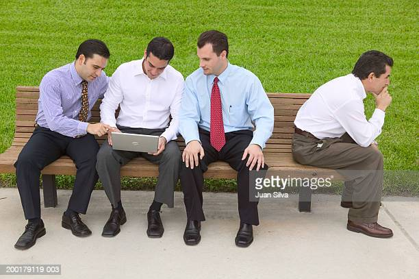 Businessmen sitting on park bench, one with laptop computer