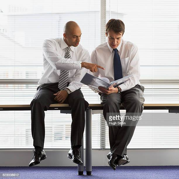 businessmen sitting on table - hugh sitton stock pictures, royalty-free photos & images